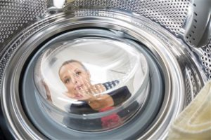 Woman's reflection in a laundry machine
