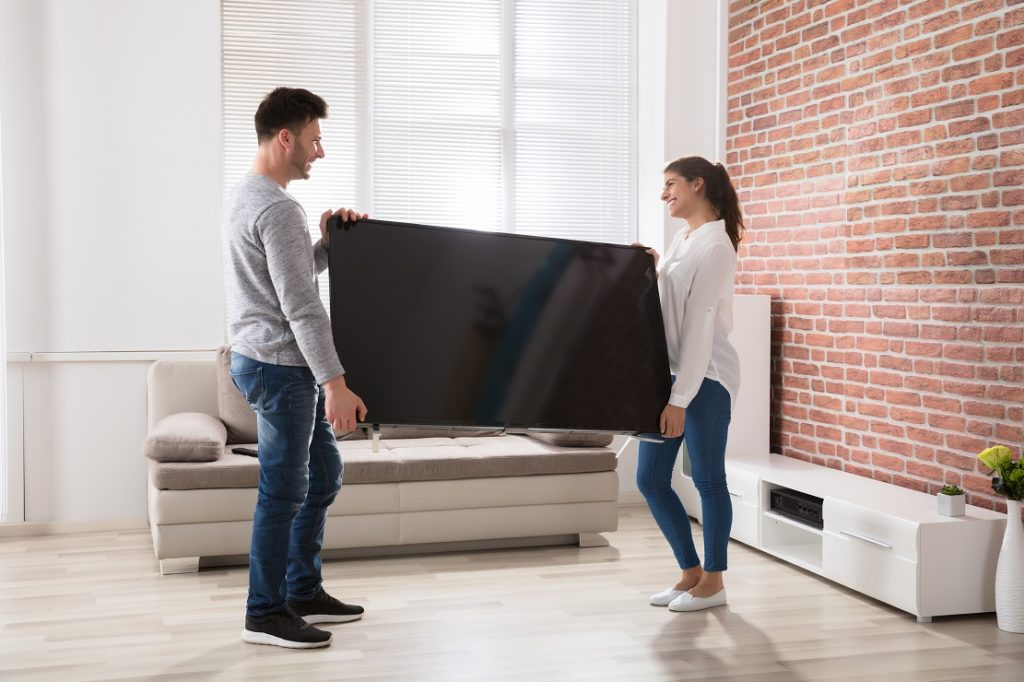 Couple Holding Television At Home