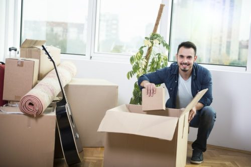 Handsome young man is moving, holding a cardboard boxes