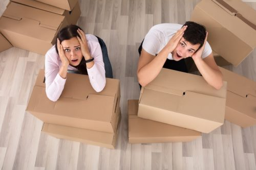 Couple Screaming Behind The Cardboard Boxes