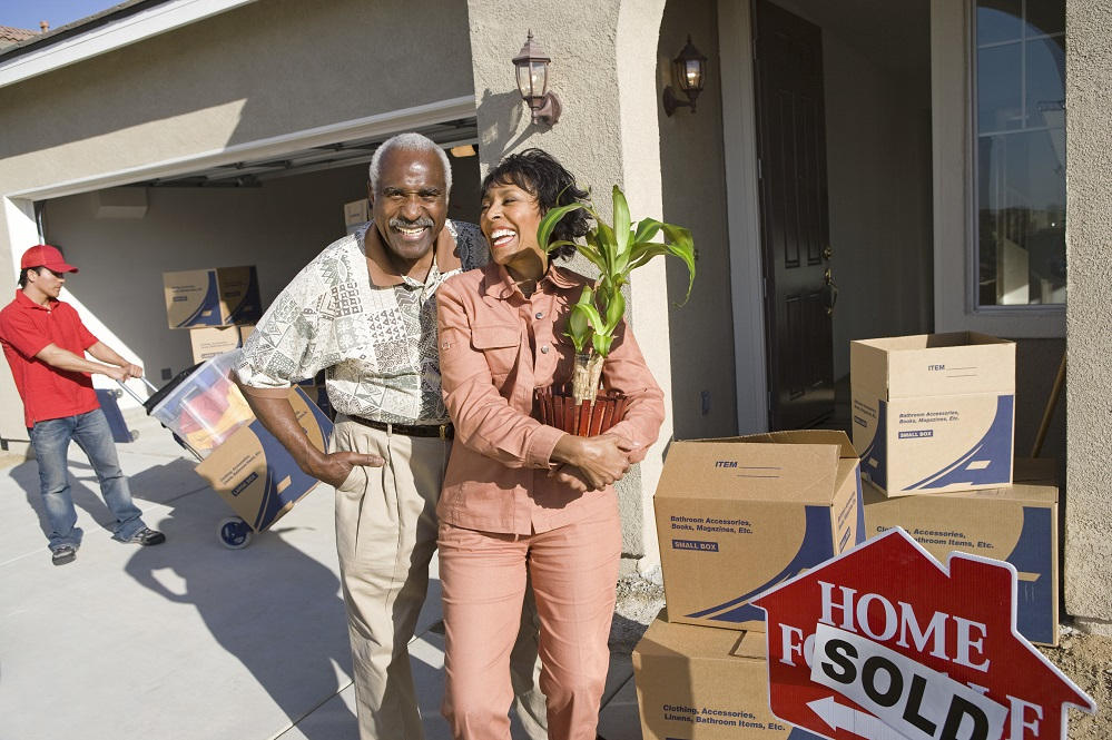 Cheerful African American couple with belongings moving into a new house title=