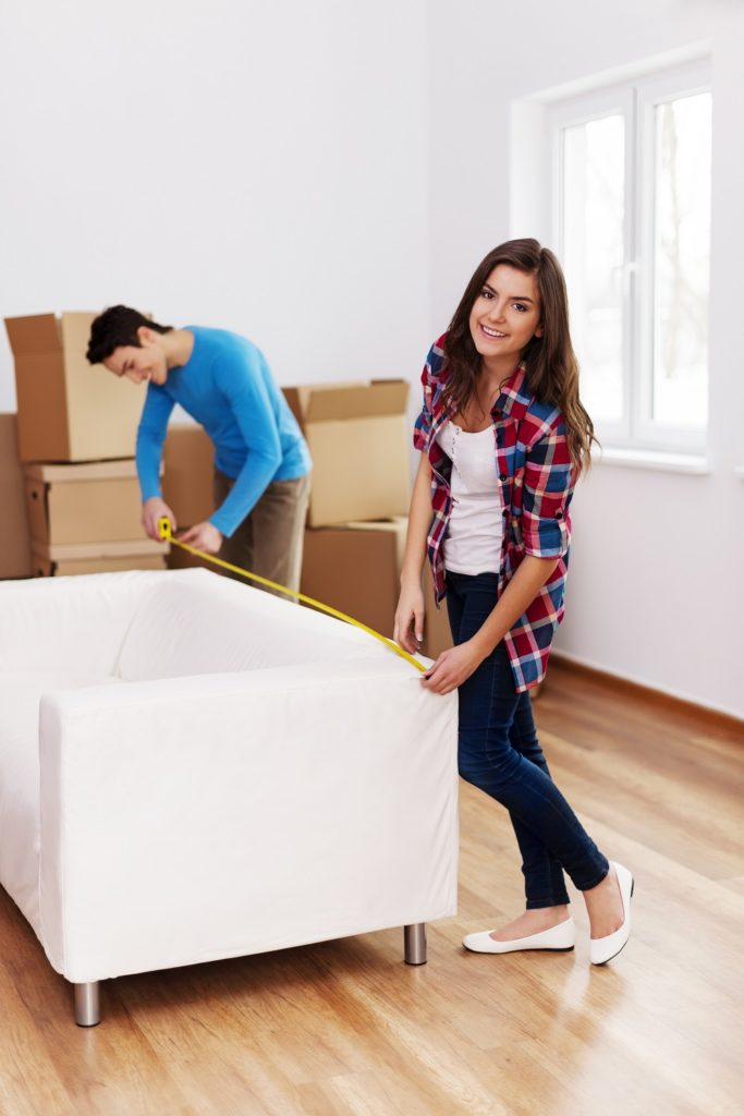 Young couple measuring the sofa their new apartment